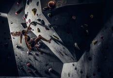 Młoda kobieta jest ubranym sportswear ćwiczy pięcie na ścianie indoors zdjęcia stock