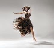 Młoda kobieta jest ubranym suknię robić włosy Fotografia Stock
