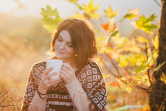 Młoda kobieta jest ubranym trykotowego poncho ma pinkin w lesie: pijący herbaty i podnosić jabłka fotografia stock