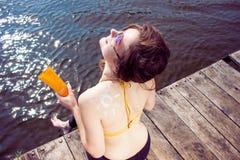 Młoda kobieta jest ubranym w żółtym swimsuit z słońce kształtem na ramieniu na plaży zdjęcie stock