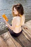 Młoda kobieta jest ubranym w żółtym swimsuit z słońce kształtem na ramieniu na plaży obrazy royalty free