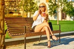 Młoda kobieta jest usytuowanym na ławce i opowiada na jej telefonie obraz royalty free