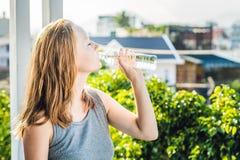 Młoda kobieta jest wodą pitną na zmierzchu tle Obraz Stock
