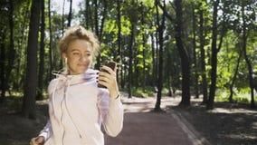 Młoda kobieta jogging w parku i wideo gawędzeniu zdjęcie wideo