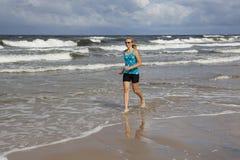 Młoda kobieta jogs wzdłuż burzowego morza zdjęcie stock