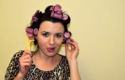 Młoda kobieta kędziorki które nawijają up na włosianych curlers włosy Zdjęcia Stock