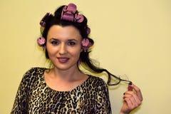 Młoda kobieta kędziorki które nawijają up na włosianych curlers włosy Zdjęcie Stock