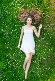 Młoda kobieta kłaść na trawie w białej sukni fotografia stock