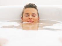 Młoda kobieta kłaść pod wodą w wannie Zdjęcia Stock