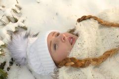 Młoda kobieta kłama w śniegu fotografia stock