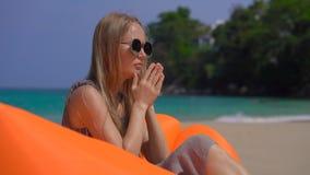 Młoda kobieta ka podczas gdy siedzący na nadmuchiwanej kanapie na tropikalnej plaży podróży choroby pojęcie zbiory
