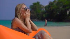 Młoda kobieta ka podczas gdy siedzący na nadmuchiwanej kanapie na tropikalnej plaży podróży choroby pojęcie zdjęcie wideo