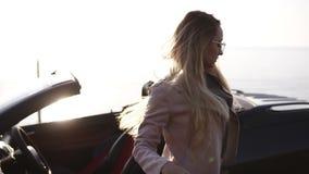 Młoda kobieta kierowca w beżowej skórzanej kurtce z długie włosy i eleganckimi okularami przeciwsłonecznymi otwiera drzwi jej kab zbiory wideo