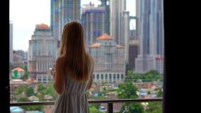 Młoda kobieta komes balkon jej mieszkanie z widokiem na centrum miasta pełno skyscrappers i napoju ranek zdjęcie wideo