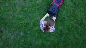Młoda kobieta kosi zielonej trawy w jej swój homeyard z gazonu kosiarzem 4K zdjęcie wideo