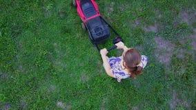 Młoda kobieta kosi zielonej trawy w jej swój homeyard z gazonu kosiarzem 4K zbiory