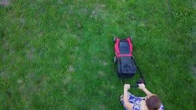 Młoda kobieta kosi zielonej trawy w jej swój homeyard z gazonu kosiarzem 4K zbiory wideo