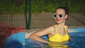Młoda kobieta która cieszy się chłodno wodę w basenie relaksuje w lato czasie zbiory