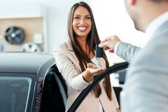 Młoda kobieta kupuje jej pierwszy brandnew samochód fotografia stock