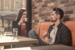 Młoda kobieta mężczyzna kawiarnia indoors pije opowiadać Zdjęcie Stock