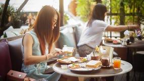 Młoda kobieta ma śniadanie w plenerowej kawiarni przy chiangmai miastem Tajlandia, miękka ostrość fotografia stock