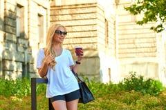 Młoda kobieta ma kawę przed starym budynkiem zdjęcie royalty free