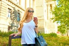 Młoda kobieta ma kawę przed starym budynkiem obrazy stock