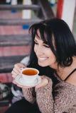 Młoda kobieta ma pinkin: pić herbacianą i czytelniczą książkę Obrazy Stock