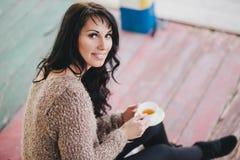 Młoda kobieta ma pinkin: pić herbacianą i czytelniczą książkę Zdjęcia Stock