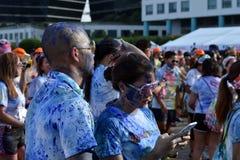 Młoda kobieta ma zabawę z smartphone przy koloru Manila błyskotliwości bieg wydarzenia społeczeństwo Zdjęcia Royalty Free