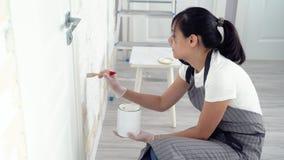 Młoda kobieta maluje ścienną farbę w domu lub mieszkaniu zdjęcie wideo