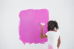 Młoda kobieta maluje jej ścianę w menchiach zdjęcie stock