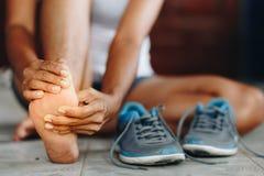 Młoda kobieta masuje jej bolesną stopę od ćwiczyć i runni fotografia stock