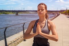Młoda kobieta medytuje w mieście rzeką w lecie, zamknięty ey Zdjęcia Royalty Free