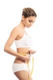 Młoda kobieta mierzy jej brzucha w sporty ubraniach obrazy stock