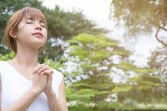 Młoda kobieta modli się publicznie parka azjatykcia dziewczyna składał ona ręki Obraz Stock