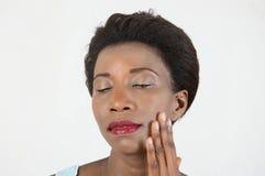 Młoda kobieta muska jej twarz fotografia stock