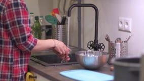Młoda kobieta myje warzywa w kuchennym zlew zbiory