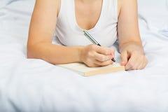 Młoda kobieta na łóżku z notatnikiem Obrazy Stock