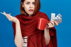 Młoda kobieta na błękitnym tle w szaliku trzyma kubek, pigułki, termometr, portret, choroba, grypa obraz stock