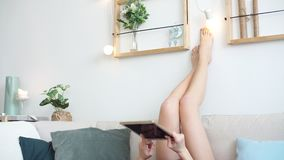 Młoda kobieta na kanapie używa pastylki relaksować i komputer w domu zdjęcie wideo
