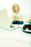 Młoda kobieta na kanapie z gadżetami Obrazy Royalty Free