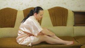Młoda kobieta na leżance w domu stosuje talku proszek na skórze ona po depilacji nogi zdjęcie wideo