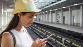 Młoda kobieta na overground staci metru Żeński turystyczny use telefon komórkowy podczas gdy czekający pociąg zbiory wideo