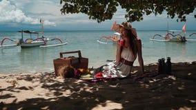 Młoda kobieta na plażowym pinkinie pije sok pod drzewem zdjęcie wideo