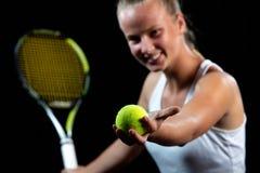 Młoda kobieta na tenisowej praktyce Beginner gracz trzyma kant, uczy się podstawowe umiejętności czarny tło portret obrazy stock