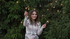 Młoda kobieta na tle girlandy z sparklers i choinka zabawa i skoki zdjęcie wideo
