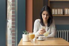Młoda kobieta napoju kawa i use smartphone przy kawiarnią Fotografia Royalty Free