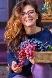 Młoda kobieta - nastoletnia dziewczyna z długim, falistym włosy, będący ubranym szkło, trzymający winogrono, ono uśmiecha się, si Obrazy Royalty Free