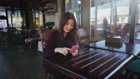 Młoda kobieta nauczyciel sprawdza testy w cukiernianym używa smartphone zdjęcie wideo